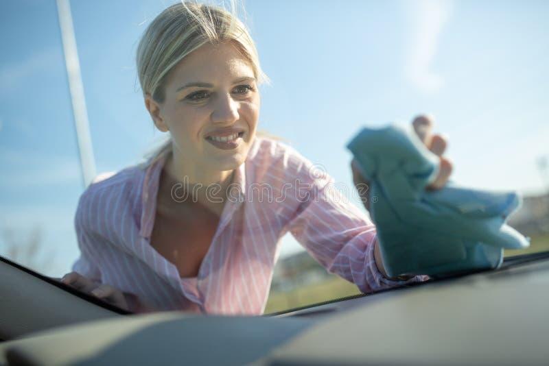 Menina loura na camisa cor-de-rosa que lustra o para-brisa fotos de stock royalty free