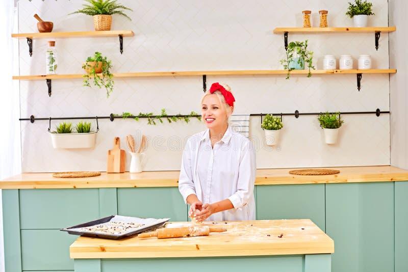 A menina loura na cozinha amassa a massa Ao lado do fog?o, cozinha imagens de stock royalty free