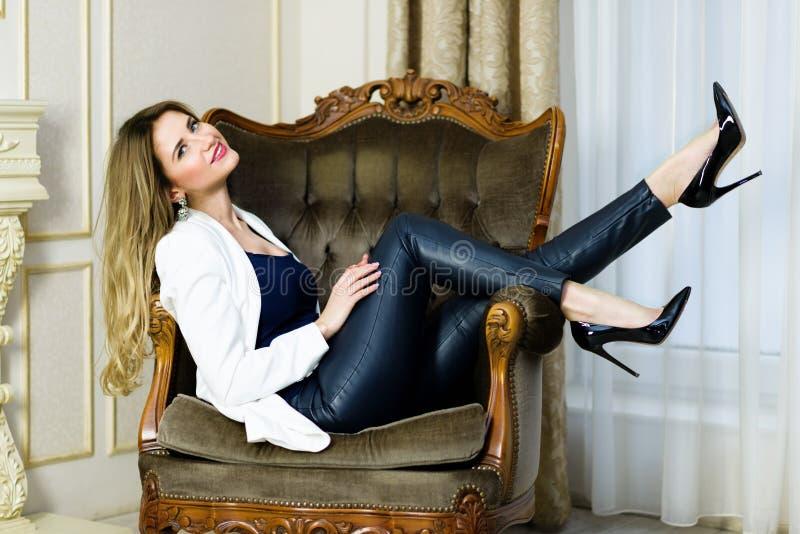 Menina loura nas calças de couro que sentam-se em um sofá imagens de stock