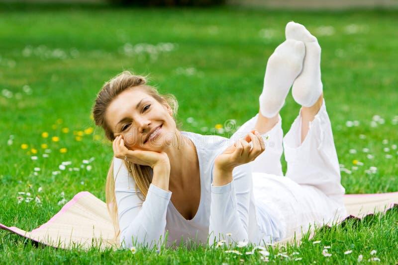 Menina loura no parque que relaxa fotografia de stock