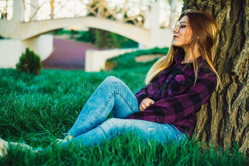 Menina loura no parque que senta-se sob uma árvore imagem de stock royalty free