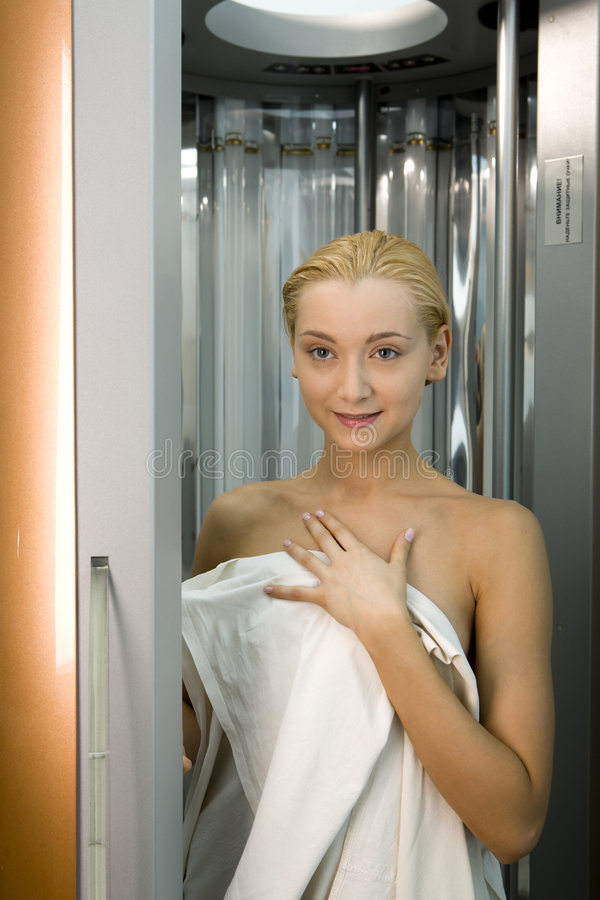 Menina loura no solarium fotografia de stock