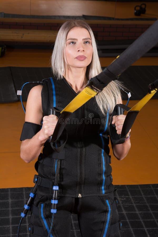 Menina loura no terno muscular bonde da estimulação que faz o exercício da ocupa para a parte traseira e com suspensão imagem de stock