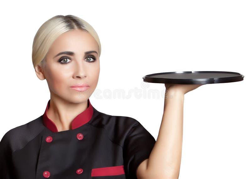 Menina loura no uniforme com uma bandeja preta vazia em sua m?o foto de stock royalty free