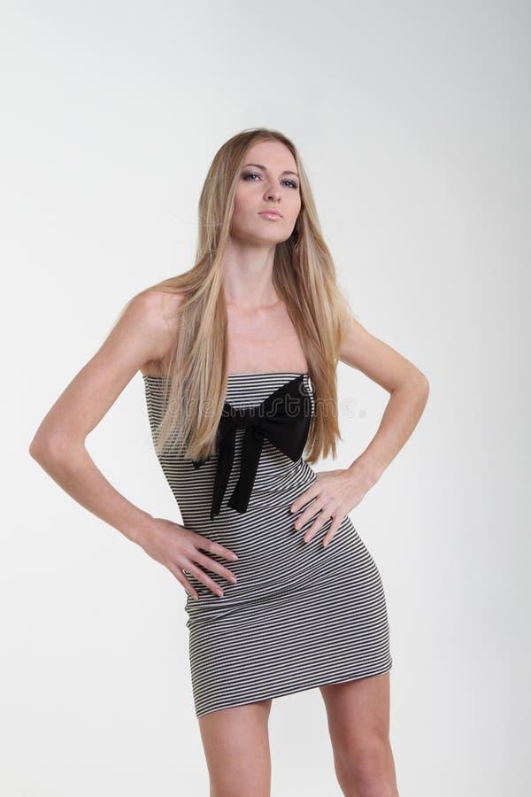 Menina loura no vestido listrado com curva preta fotografia de stock royalty free