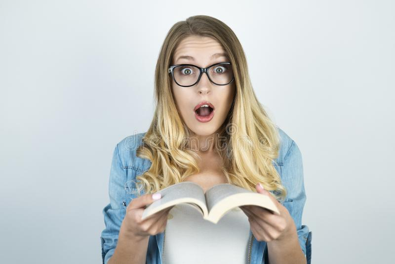 Menina loura nos vidros surpreendida guardando o livro fotografia de stock