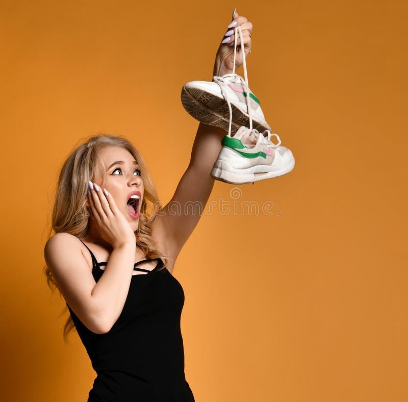 A menina loura nova é horrorizada por pares velhos de sapatas que sujas encontrou imagem de stock royalty free