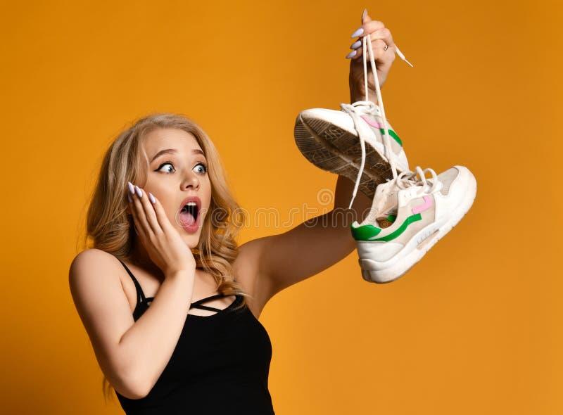 A menina loura nova é surpreendida muito por seu achado - par velho de sapatas sujas foto de stock