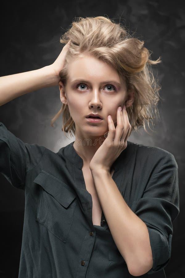 Menina loura nova bonita com penteado bagun?ado e composi??o nude, vestindo uma camisa e as cal?as de brim que levantam emocional fotografia de stock