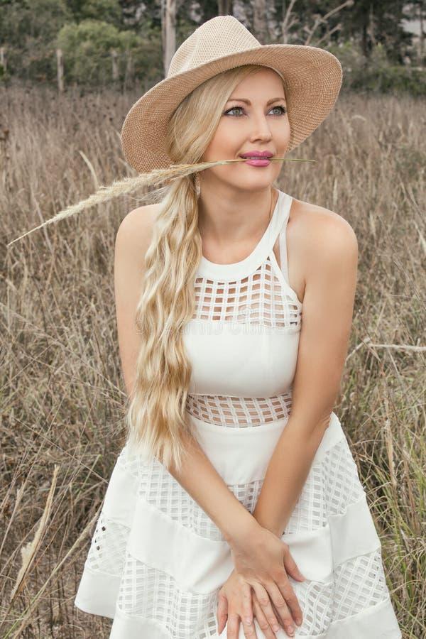 Menina loura nova bonita em um chapéu que levanta na pradaria; no fundo é um campo das orelhas imagens de stock royalty free