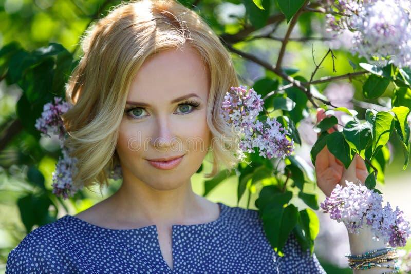 Menina loura nova bonita lindo perto do arbusto lilás fotos de stock royalty free
