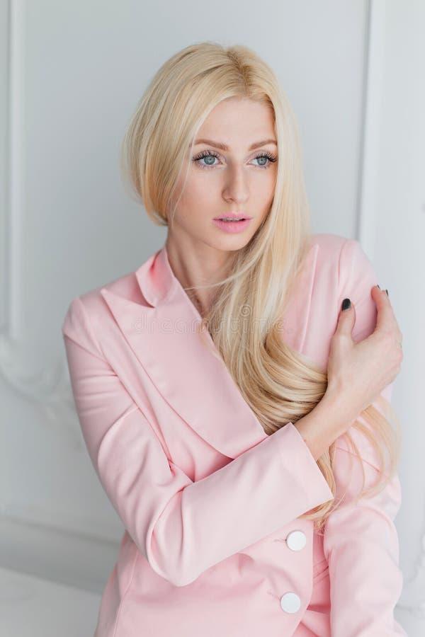 Menina loura nova bonita na roupa elegante cor-de-rosa fotografia de stock royalty free
