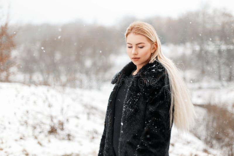Menina loura nova bonita no casaco de pele que levanta no parque do inverno imagem de stock royalty free