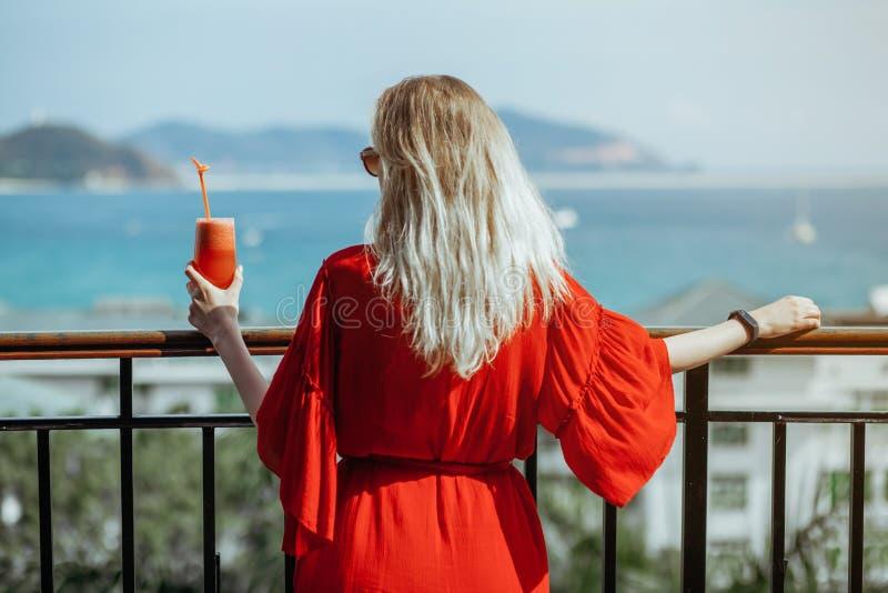 Menina loura nova bonita no vestido e em óculos de sol vermelhos que bebe o cocktail vermelho de um vidro no balcão Contra imagens de stock royalty free