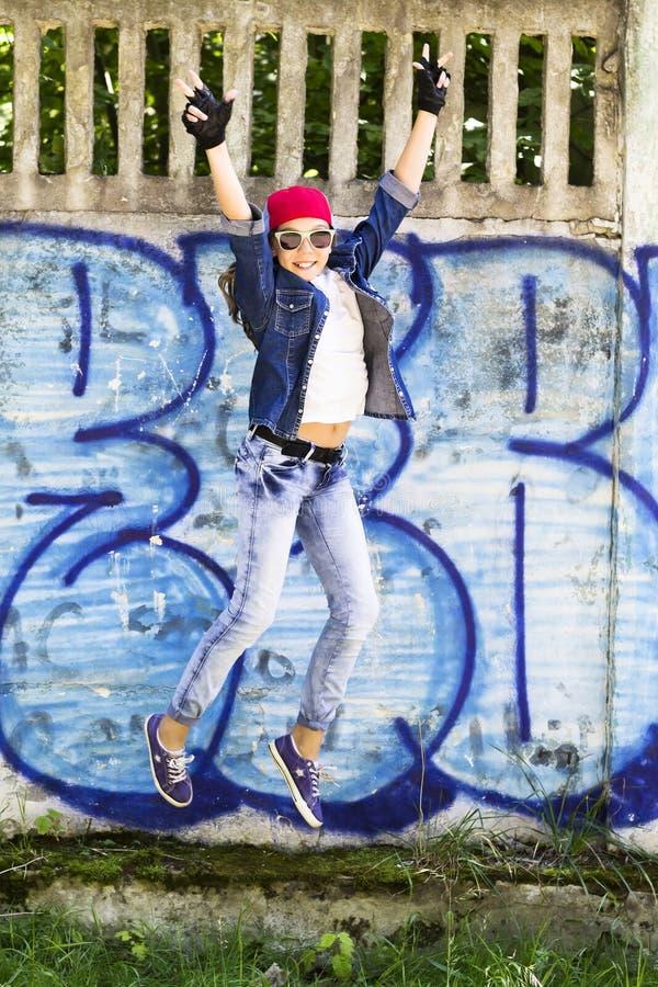 Menina loura nova bonito do adolescente em um boné de beisebol e em uma camisa das calças de brim que saltam contra um fundo da p foto de stock