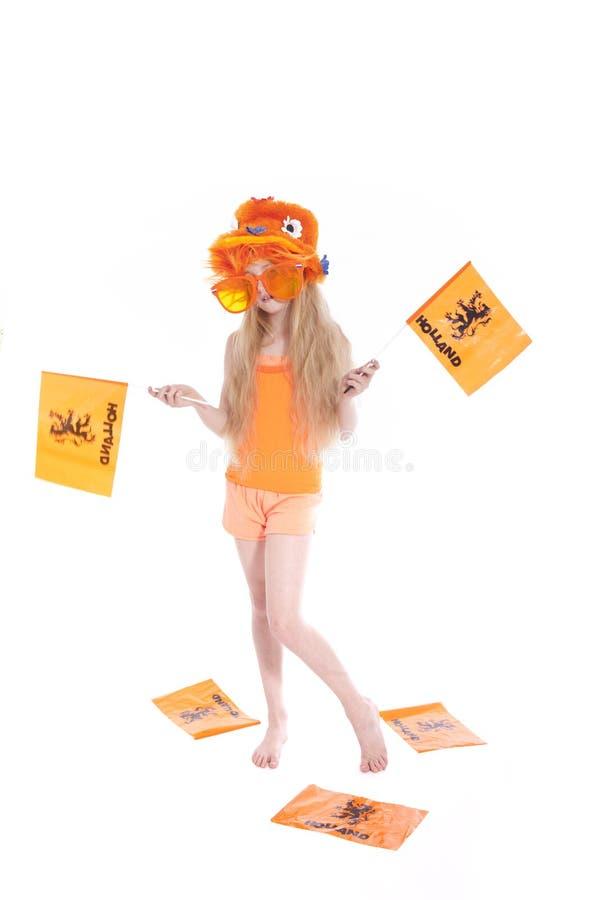 Menina loura nova com as bandeiras de ondulação do chapéu alaranjado no estúdio fotografia de stock royalty free
