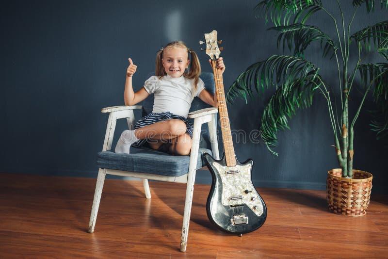 A menina loura nova com as caudas no t-shirt, na saia e nas sandálias brancos com guitarra elétrica mostra em casa o polegar que  imagem de stock royalty free