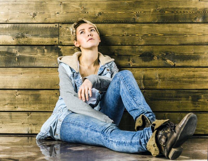 Menina loura nova com cabelo curto em um revestimento e em calças de brim da sarja de Nimes foto de stock