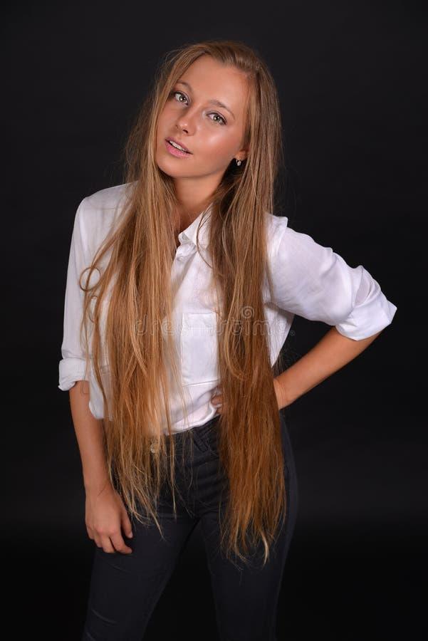 Menina loura nova de Beautyful com cabelo longo em uma camisa branca foto de stock