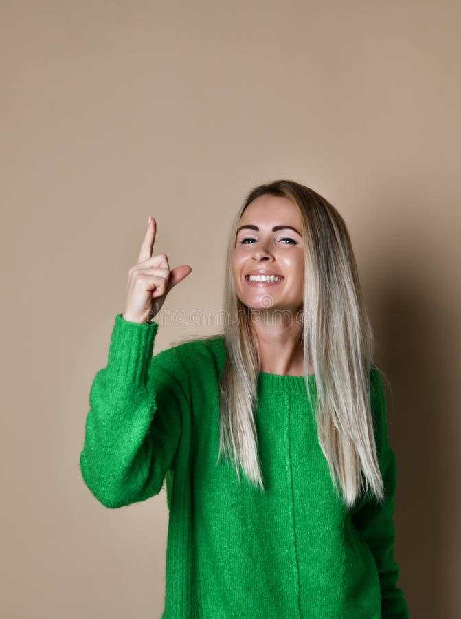 Menina loura nova de sorriso agradável no fundo bege que aponta o dedo até a atenção da tração à informação importante foto de stock