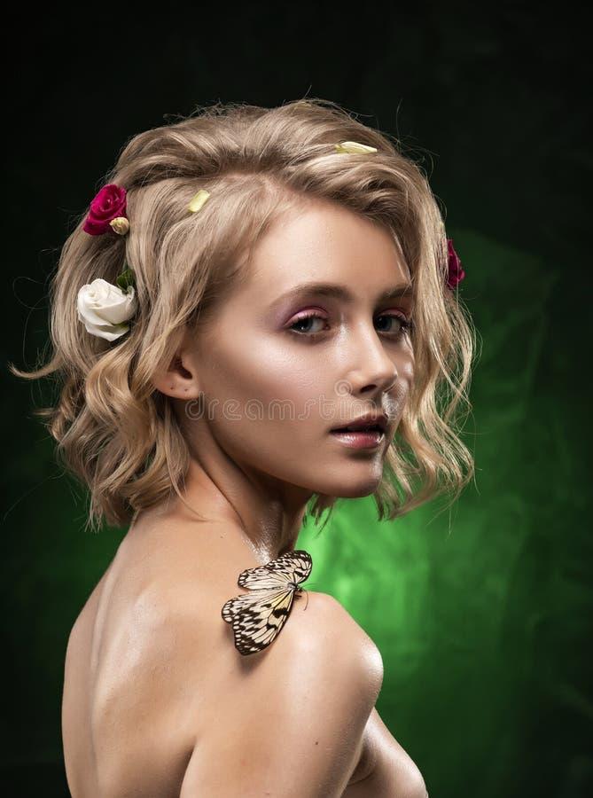 Menina loura nova de sorriso bonita com as flores tran?adas em seu cabelo, corpo oleoso e em uma borboleta em seu ombro despido e imagem de stock royalty free