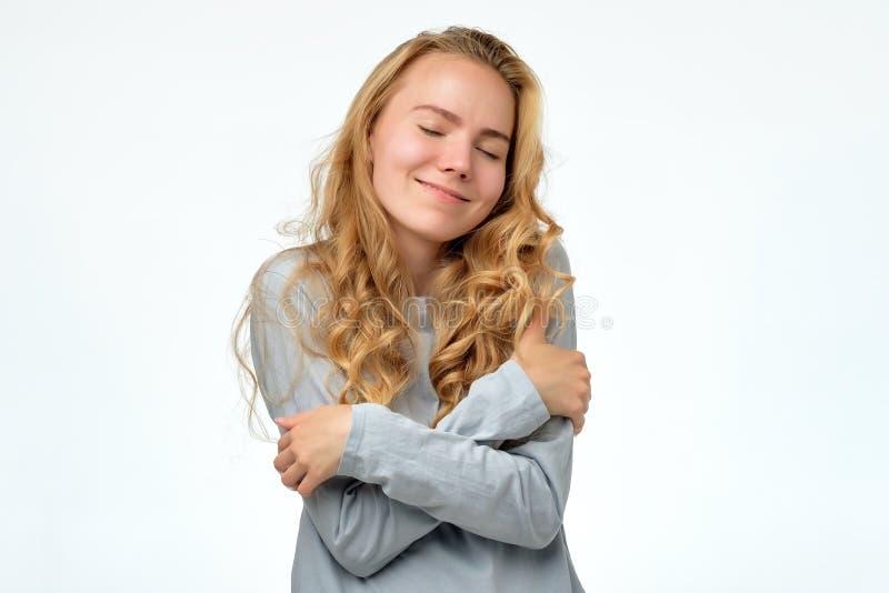 Menina loura nova do adolescente que abraçam-se oneself que está feliz e sorriso seguro fotografia de stock royalty free