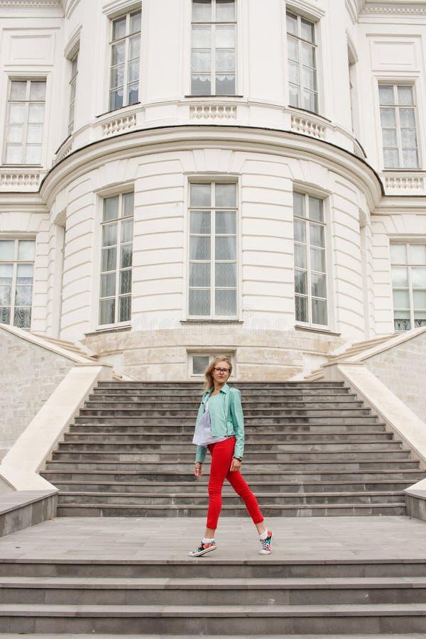 Menina loura nova elegante que levanta nas escadas Olhar à moda do ` s da mulher foto de stock