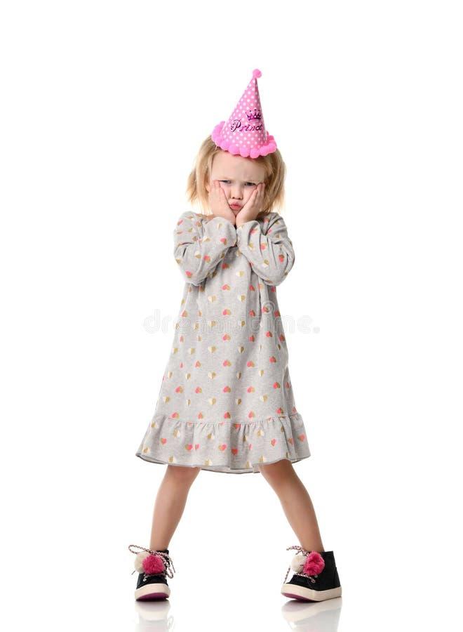 Menina loura nova em emoções tristes viradas do chapéu da princesa da festa de anos fotos de stock royalty free