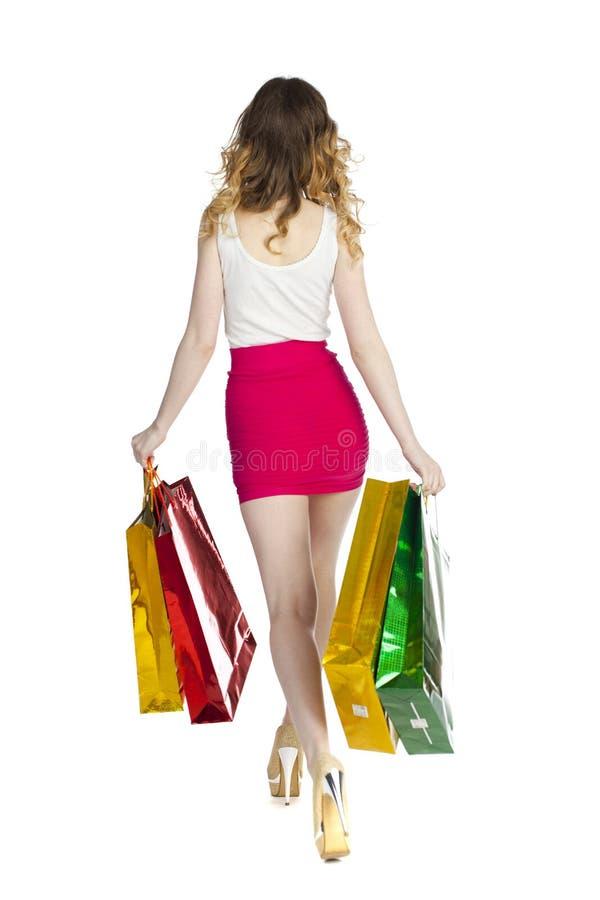 Menina loura nova feliz com os sacos de compras coloridos na saia vermelha fotografia de stock royalty free
