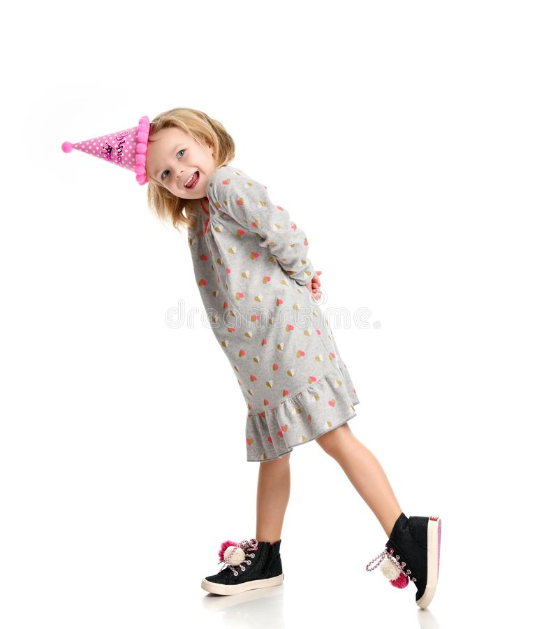 A menina loura nova nas mãos do chapéu da princesa da festa de anos espalhou acima de gritar fotografia de stock