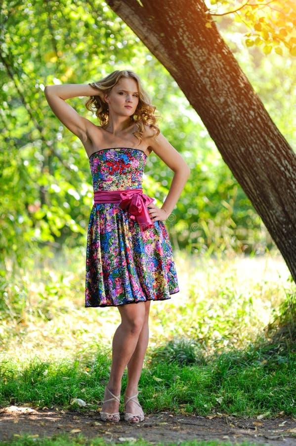 Menina loura nova no vestido colorido brilhante que levanta no parque do verão perto da árvore grande na luz solar brilhante fotografia de stock