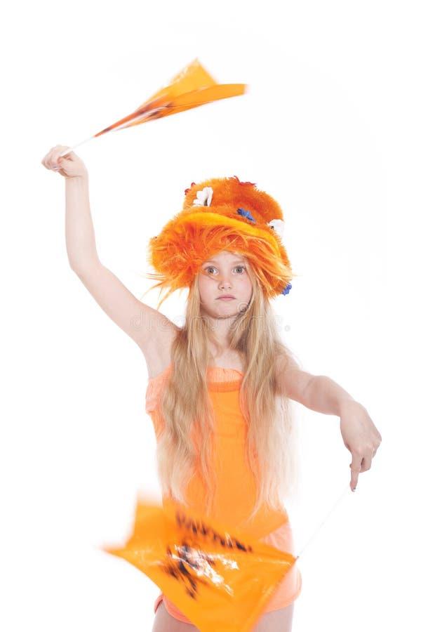 Menina loura nova que acena o chapéu e bandeiras alaranjados no estúdio imagem de stock royalty free