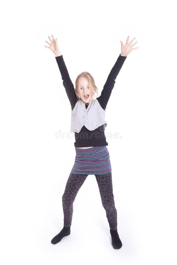 Menina loura nova que cheering com os braços aumentados no estúdio foto de stock