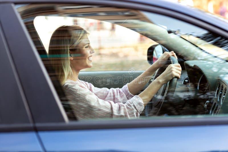 Menina loura nova que conduz com segurança seu carro imagem de stock royalty free