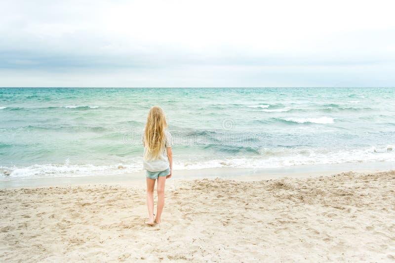 Menina loura nova que está na praia fotografia de stock royalty free