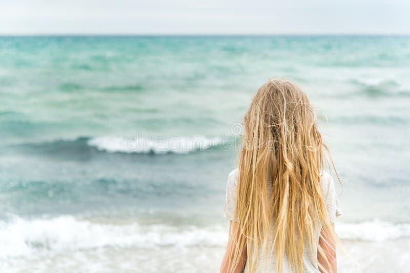 Menina loura nova que está na praia fotos de stock