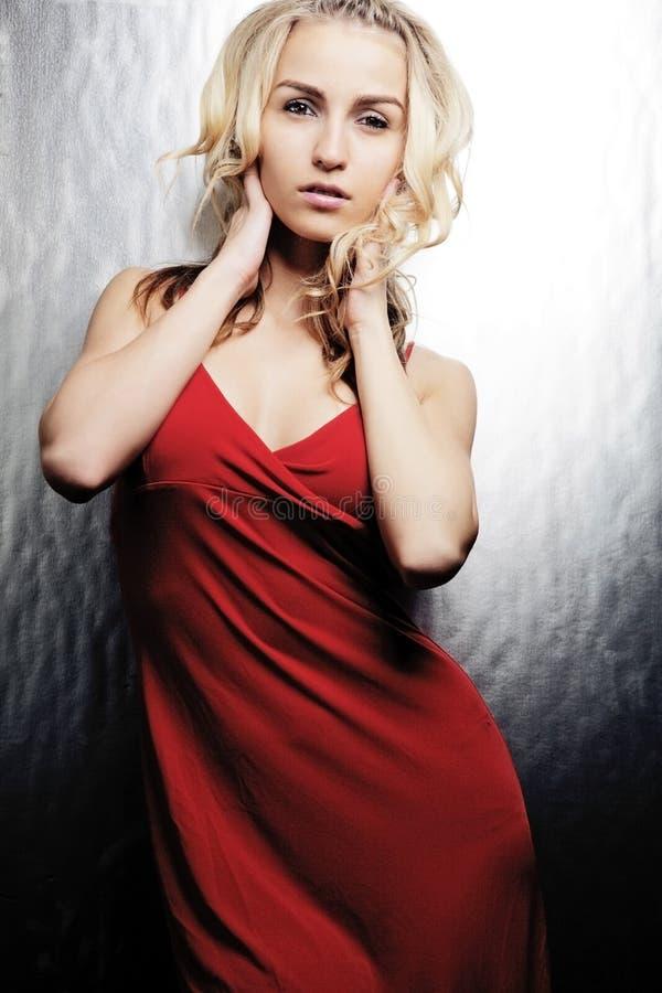 Menina loura nova que levanta no vestido vermelho. imagem de stock