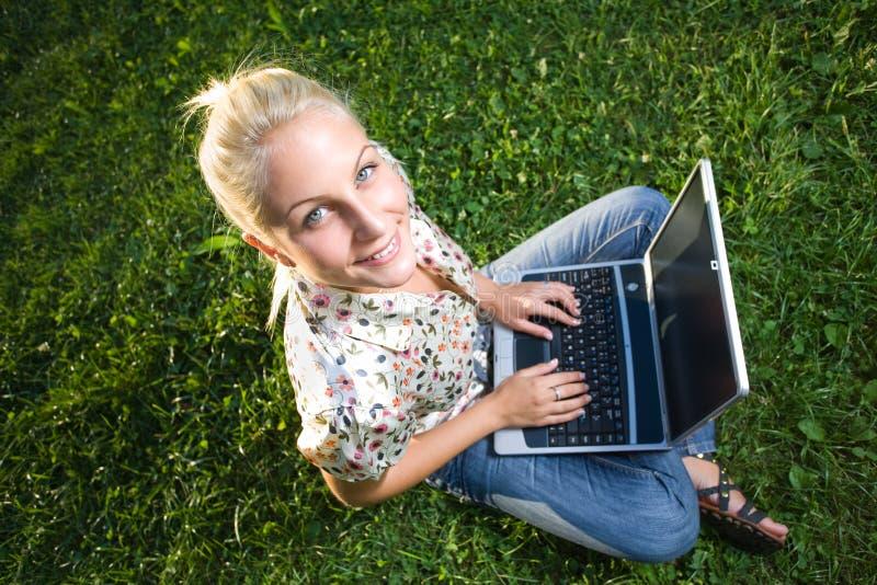 Menina loura nova que usa o portátil em parque sunlit. imagens de stock