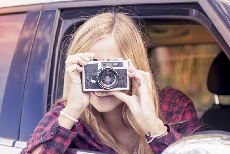 A menina loura nova toma uma foto de um carro fotos de stock royalty free
