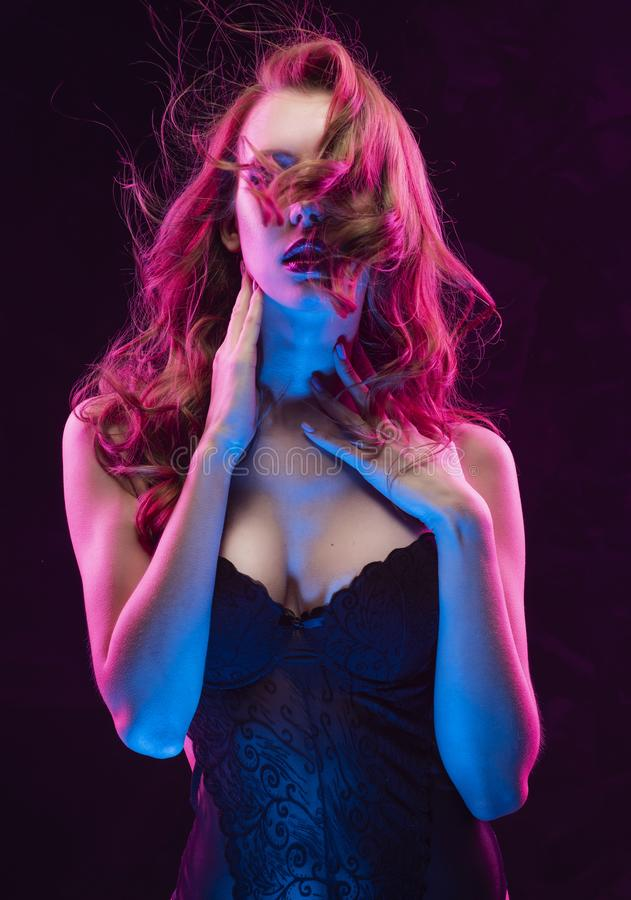 A menina loura pechugóa 'sexy' magro bonita que veste o bodysuit preto iluminado acima em sorrisos claros cor-de-rosa e azuis e t foto de stock
