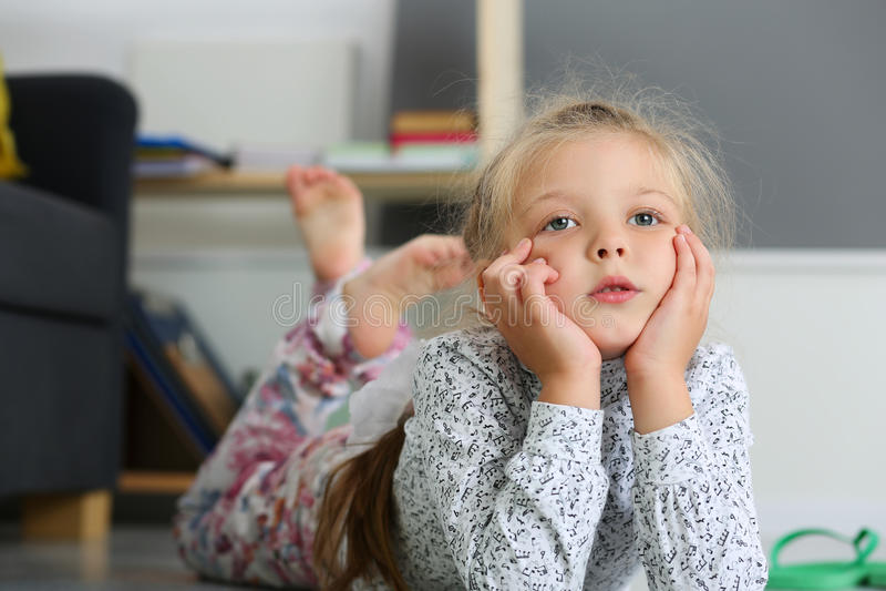 Menina loura pensativa que encontra-se no assoalho foto de stock