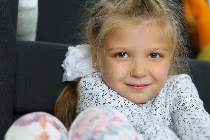 Menina loura pensativa que senta-se no assoalho fotografia de stock royalty free