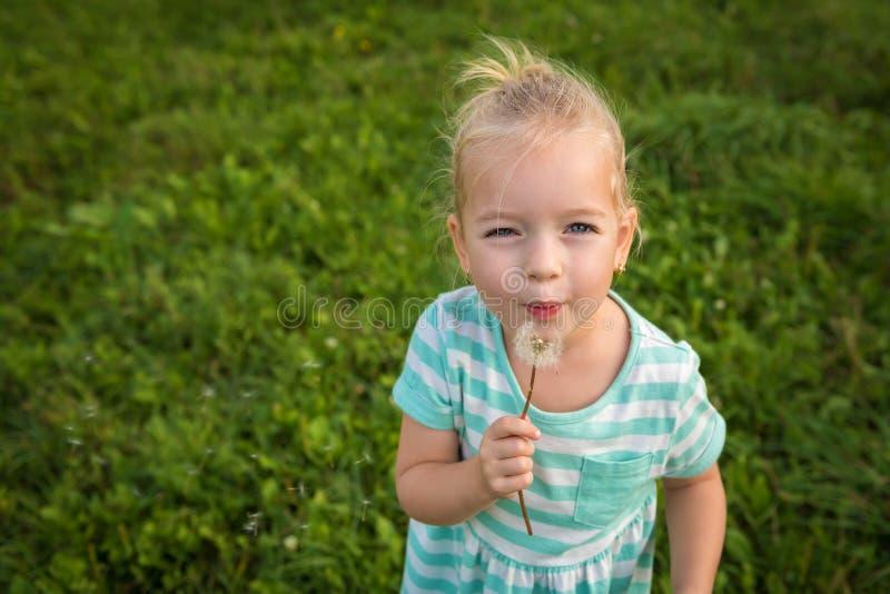 Menina loura pequena adorável com flor do dente-de-leão imagem de stock