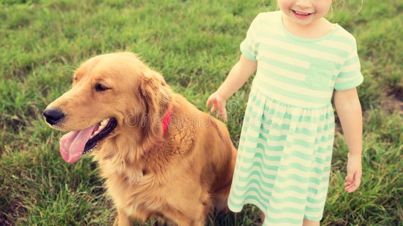 Menina loura pequena adorável que joga com seu cão imagens de stock