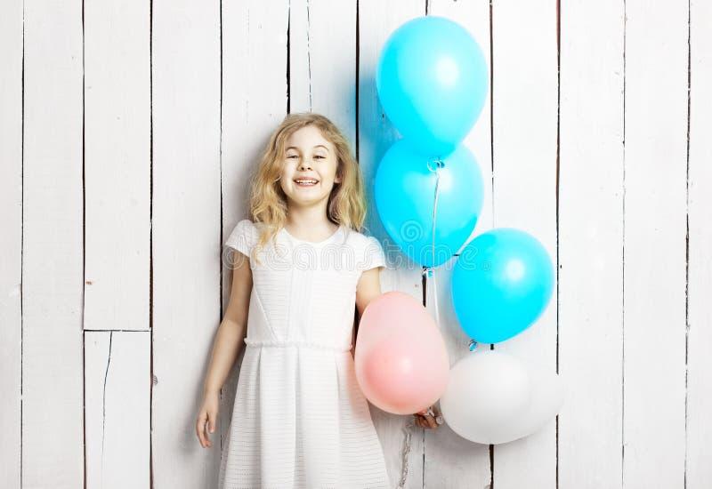 Menina loura pequena alegre com os balões no backgrou de madeira branco fotos de stock royalty free