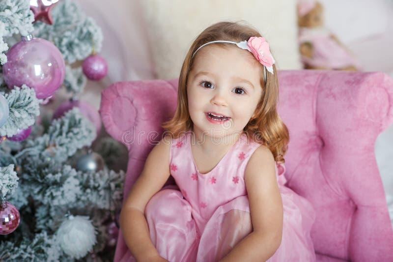 Menina loura pequena bonita com olhos marrons que sorri no ano novo no fundo da árvore de Natal foto de stock