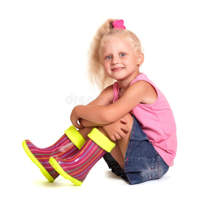 Menina loura pequena bonito assentada na blusa, na saia e nas botas de borracha imagens de stock