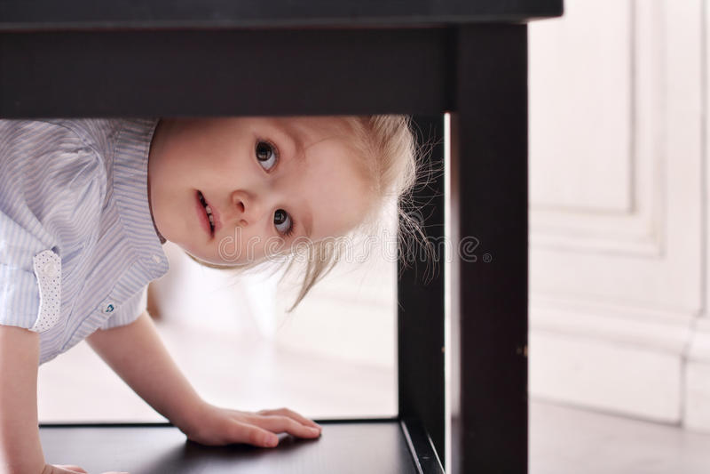A menina loura pequena bonito em camisa listrada escalou na tabela do rebaixo imagens de stock royalty free