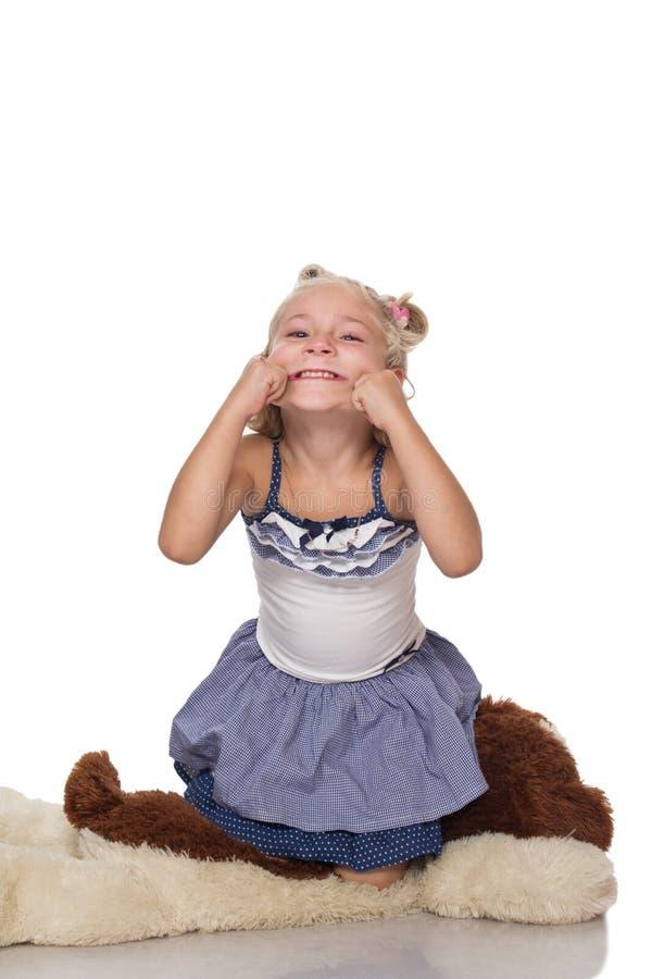 Menina loura pequena bonito que senta-se em um cão macio grande imagens de stock