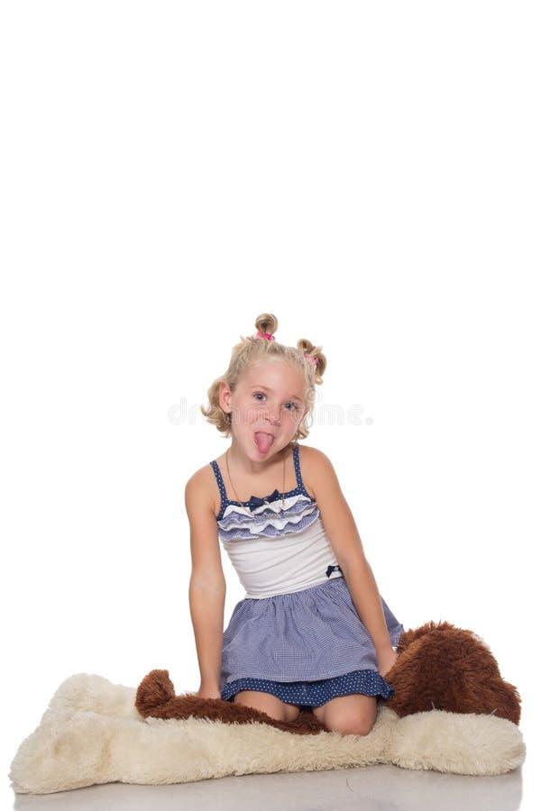 Menina loura pequena bonito que senta-se em um cão macio grande foto de stock